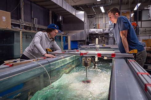 Two researchers conducting fluids research on the aerospace thermal lab
