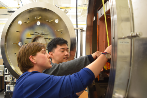 Two people working on a plasma science lab