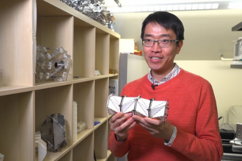 A researcher holding a chain composed of origami cells