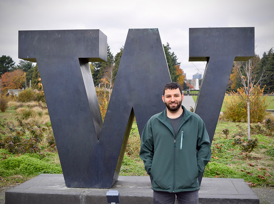 Mohammed standing in front of the W sculpture