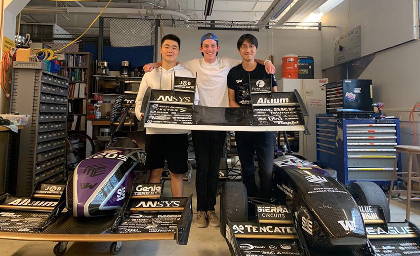 Jerry Hu, Sam Reissmann and Michael Chi posing with two race cars