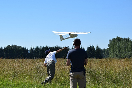 students hand launching an aircraft designed to guide itself using the onboard camera as opposed to traditional sensors such as GPS