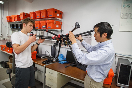 students working on a large-scale multi-rotor aircraft to be used for various applications such as radio link tests, aerial mapping, and multi-vehicle swarm operations