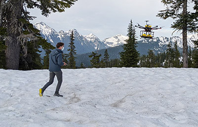 man standing on snow covered ground near a drone flying